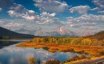 The road curves around the stunning Oxbow Bend during the peak of autumn in Grand Teton National Park, Wyoming.
