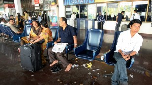"""Indian air passengers wait on benches at the domestic terminal of Netaji Subhash Chandra Bose Airport in Kolkata, on March 13, 2008 during the second day of a nationwide call to cease work by airlines workers. Water taps began running dry in some airports, litter was visible and baggage trolleys were scarce, travellers said, but airport officials said flights were still operating on schedule as airline workers observed the second day of a """"non-cooperation"""" drive to protest the opening of two private airports. AFP PHOTO/Deshakalyan CHOWDHURY (Photo credit should read DESHAKALYAN CHOWDHURY/AFP/Getty Images)"""