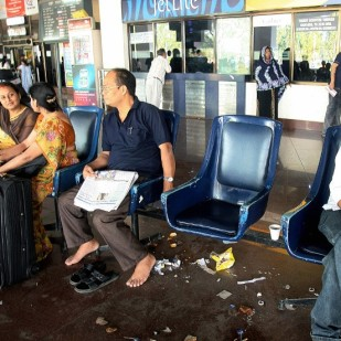 "Indian air passengers wait on benches at the domestic terminal of Netaji Subhash Chandra Bose Airport in Kolkata, on March 13, 2008 during the second day of a nationwide call to cease work by airlines workers. Water taps began running dry in some airports, litter was visible and baggage trolleys were scarce, travellers said, but airport officials said flights were still operating on schedule as airline workers observed the second day of a ""non-cooperation"" drive to protest the opening of two private airports. AFP PHOTO/Deshakalyan CHOWDHURY (Photo credit should read DESHAKALYAN CHOWDHURY/AFP/Getty Images)"