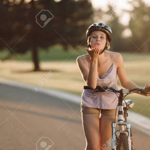 Woman with bicycle sending air kiss. Portrait of cute girl riding on bike outdoors. People and healthy lifestyle.
