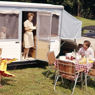1960s FAMILY WITH THREE DAUGHTERS AT TABLE BY AUTOMOBILE AND TRAILER FIVE EATING FOOD VACATION MAN WOMAN GIRL. H. ARMSTRONG ROBERTS/CLASSICSTOCK/Everett Collection (kc3535)