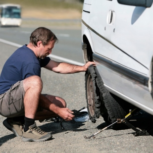 Man changes Flat Tire by the Highway